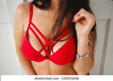 Close up of breast of woman presenting her bra. Red bra. Sexy boobs. Woman with big natural sexy boobs in lingerie. Closeup of sexy female boob in red bra. Red colored nails