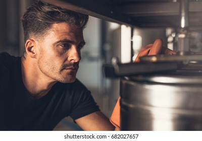 Close up of brewer working at brewery. Male brewer working with brewery equipment.