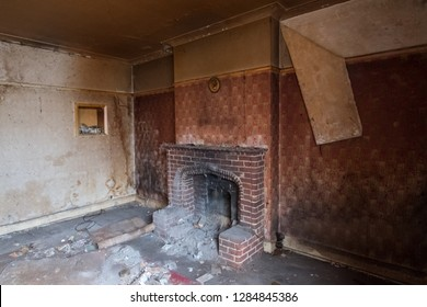 Close up of brick fireplace and peeling wallpaper in lounge in derelict 1930s deco style house, Rayners Lane, Harrow, Middlesex, UK