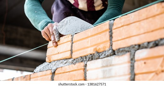 Close up of bricklayer worker's hand installing red brick with trowel putty knife for new house building at construction site.