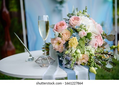 Close up of bridal bouquet of pink and blue flowers, glass of champagne and wedding rings on white wood table outdoors, copy space. Wedding concept