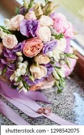 Close up of bridal bouquet of pink roses, peonies, purple flowers and herbs and two golden rings on marble window sill, copy space. Wedding concept. Selective focuse