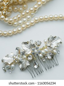 Close up of bridal jewelry detail hair pin with diamond embellishments and pearl necklace