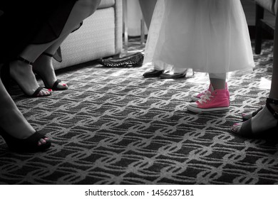 Close up of bridal partys feet in black and white with pink nail polish and flower girl with tutu dress in the middle of all the bridesmaids shoes with pink kids sneakers