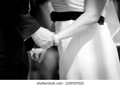 A close up of the bride and groom facing each other while holding hands, in black and white
