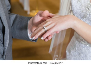 Close up of bride and groom hands. Groom has just placed bridal wedding band and engagement ring on his fiancee during inside church ceremony.