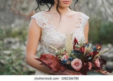 Close up of a bride holding colorful elegant modern fall wedding bouquet in red, marsala, burgundy for a autumn wedding