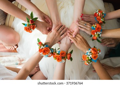 Close up of bridesmaids holding bride's hands