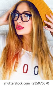 Close up bright fashion portrait of stylish hipster girl in glasses and hat, have sexy smile , full red lips and long blonde hairs, white background.