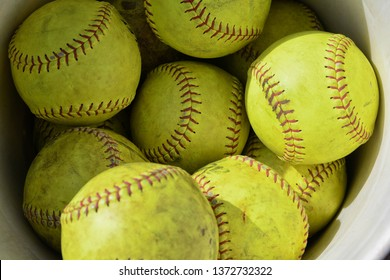 close up of bright yellow used softballs with red stiching