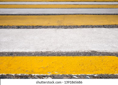 Close up of bright yellow and white stripes of zebra crossing, pedestrian crosswalk.