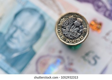 A close up of a British Pound Coin on top of bank notes