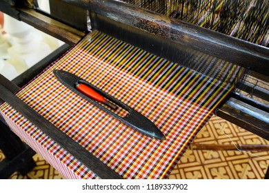 Close up of brocade fabric weaving on loom, cotton on the manual wood loom in Vietnam traditional culture. Multi-colored brocade threads on a loom.