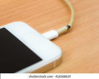 Close of broken charger cable with smart phone on the wooden table