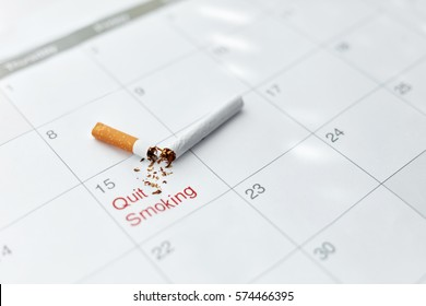 Close Up Of Broken Cigarette Lying On Month Calendar. Quit Smoking Cigarettes Concept. High Resolution