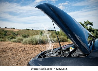 Close up of a broken down car, engine open with smoke, in a rural area