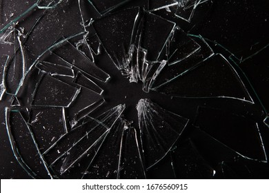 Close up of broken glass on dark background with lots of glass splinters