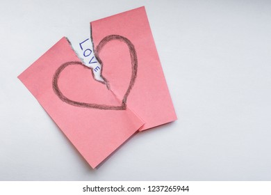 close up of a broken heart drawn on a pink sticker as a symbol of unrequited love. love breaks the heart concept. The symbol of problems in romantic relationships between people