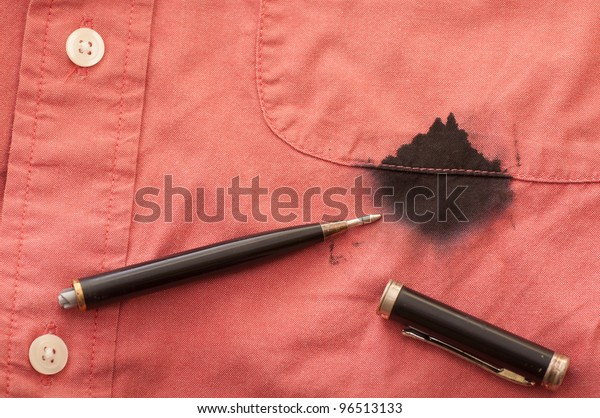 A Close Up of a Broken Pen Resting on the Men's Red Shirt Stained with Ink