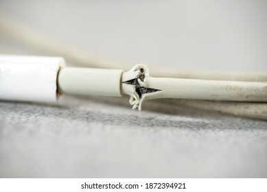 Close up of broken smart phone charger cable on light background