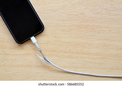 Close Up the Broken Smart Phone Charger Cable on wooden Background.