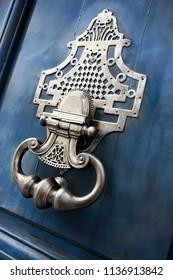 Close up of a bronze knocker on a wooden door