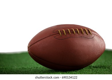 Close up of brown American football on field against white background