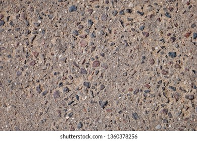 Close up of brown asphalt with colored stones. Rough surface. Abstract textured background
