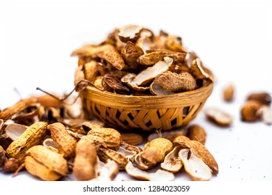 Close up of brown colored hamper having groundnuts or peanuts or moongaphalee or Arachis hypogaea or goober or monkey nut some in shells and some opened isolated on white.