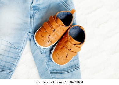 Close up brown leather kids shoes and denim pants.  Top view fashion trendy look of baby clothes, fashion concept
