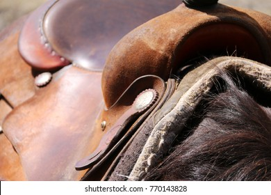 Close up of brown leather western saddle on a black horse.