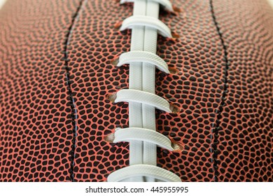 Close up of brown leather and white laces of American Football.