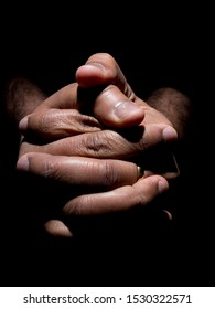 Close up of a brown mans clasped hands in low key lighting
