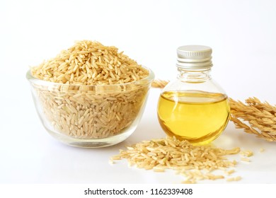 Close up brown rice seed and rice bran oil in bottle  and unmilled rice on white background , good fats for healthy food