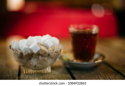 Close Up Brown And White Sugar Cubes with cup of Tea isolated on red background