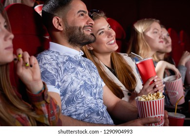 Close up of brunette Arabian man in printed blue shirt and blonde smiling woman looking at screen in cinema, Couple of positive friends having fun, spending time together. Concept of enjoyment,
