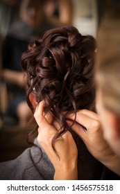Close up of brunette bride with hair stylists hands finishing curly updo for wedding day
