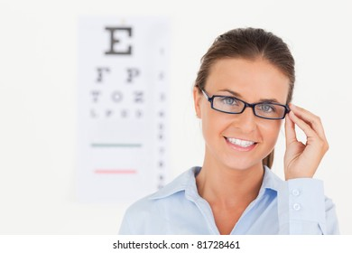 Close up of a brunette eye specialist wearing glasses looking into the camera in the surgery