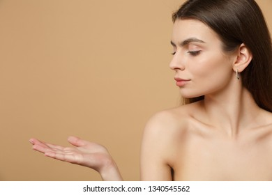 Close up brunette half naked woman 20s with perfect skin, nude make up isolated on beige pastel wall background, studio portrait. Skin care healthcare cosmetic procedures concept. Mock up copy space