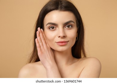 Close up brunette half naked woman 20s with perfect skin, hand on cheek isolated on beige pastel wall background, studio portrait. Skin care healthcare cosmetic procedures concept. Mock up copy space