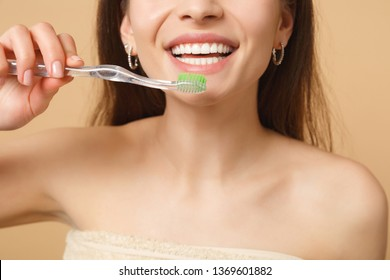 Close up brunette half naked woman 20s with perfect skin, nude make up hold brush isolated on beige pastel wall background studio portrait. Health care cosmetic procedures concept. Mock up copy space