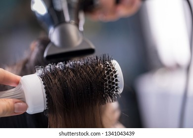 Close up of brunette long-haired lady getting new hairstyle in barber shop. Professional hairdresser using blow dryer and hairbrush while styling hair of female client. Focus on round hairbrush