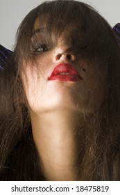 close up of brunette with red lips and long looking like a witch
