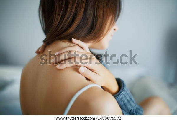 Close up of a brunette woman massing her neck in a bedroom