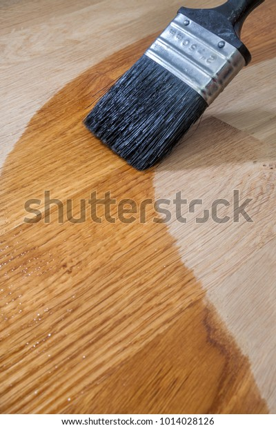 Close up a brush applying wood oil onto a solid Oak surface