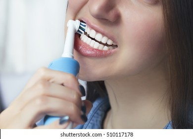 Close up of brushing teeth with electric toothbrush. Young woman