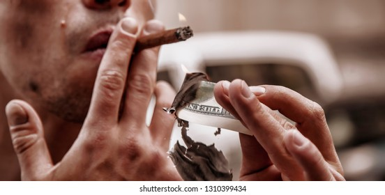 Close up brutal businessman lighting cigar with $100 dollar bill. Selective focus on the mburning money.