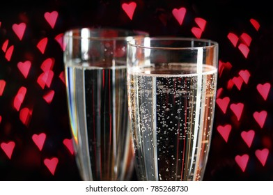Close up of bubbles of sparkling wine or champagne in two flutes against heart shape red lights for Valentine's Day