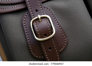 Close up of buckle on green khakis fabric and chocolate leather trim color.