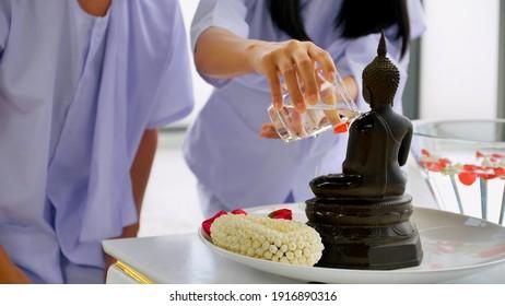 Nahaufnahme des Buddhismus, der am Songkran-Tag oder am Thai-Neujahr Wasser in das Buddha-Bild gießt.